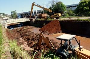 Enquanto a escavadeira coloca a sujeira nos caminhões, uma retro fica dentro do rio limpando as encostas do muro de contenção